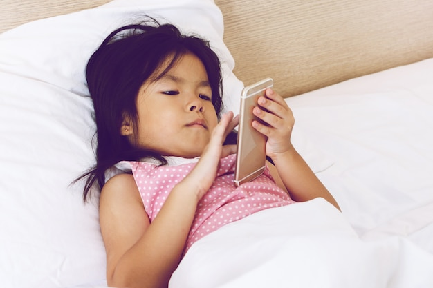 Children girl texting on smartphone and lying in bed at home