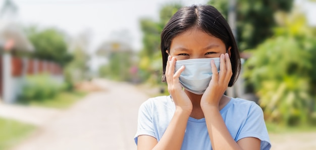 フェイスマスクを身に着けている子供女の子はcovid 19の大気汚染およびウイルスの伝染病を保護します