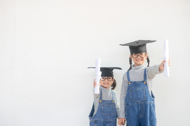 Children girl wearing a graduate cap over white background very happy and excited