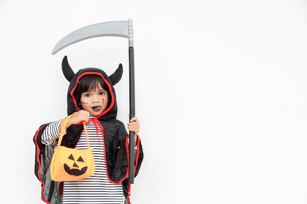 Children girl wearing mysterious halloween dress holding a scary pumpkin and sickle.