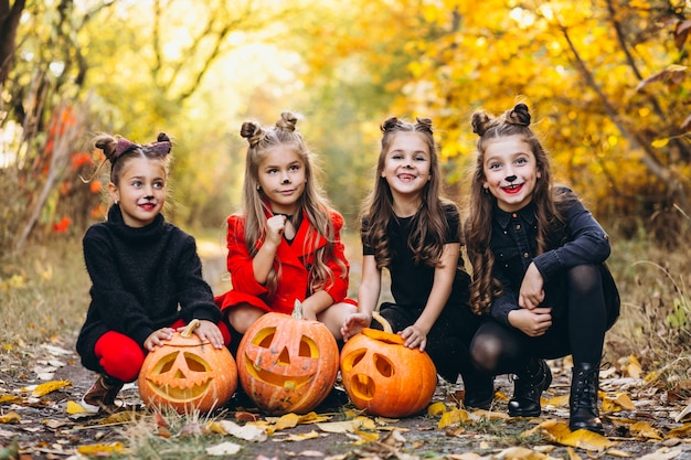 Children girls dressed in halloween costumes outdoors with pumpkins