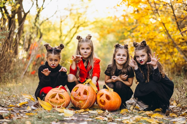 Children girls dressed in halloween costumes outdoors with pumpkins
