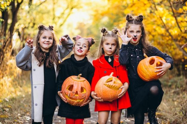 Дети девочки одеты в костюмы хэллоуина на открытом воздухе с тыквами