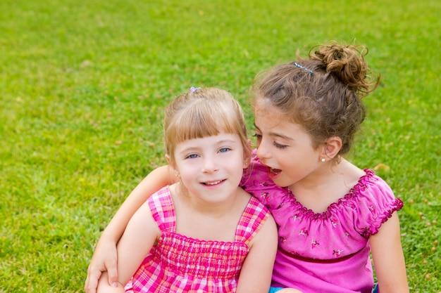 Children girls hug in green grass