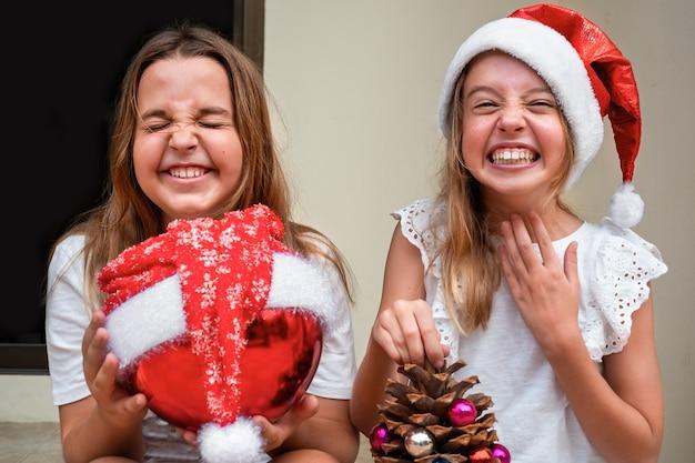 Дети девушки в новогодних шапках сидят на крыльце с елочными украшениями