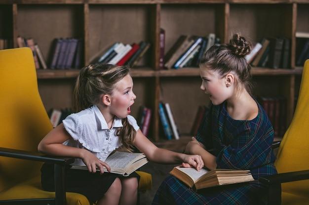 교육에서 엄격한 방식으로 책이 있는 도서관의 어린이 소녀들