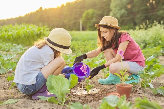 Дети девочки сажают цветущее горшечное растение в землю.