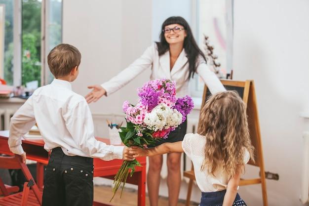 Children give flowers as a school teacher in teacher's day
