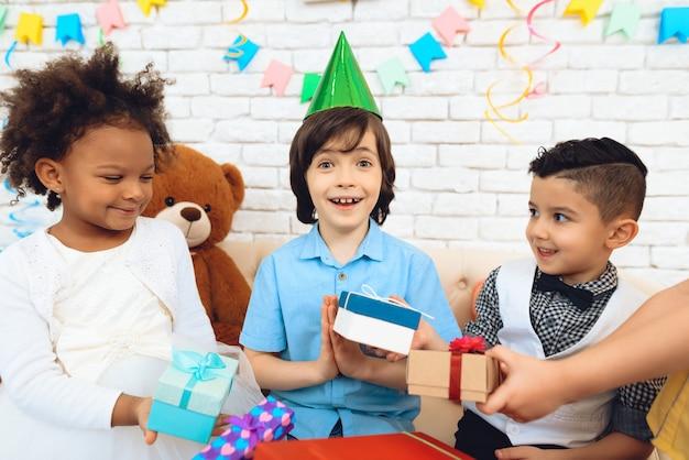 Children gives presents to birthday boy in festive hat.