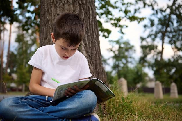 子供たちは学校に戻ります。夏休みから新学期が始まります。愛らしいハンサムな男子生徒、初日の授業の合間にレクリエーション中に宿題をしている小学生の子供