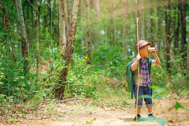 Children go hiking at backyard with backpacks at forest path explorer and adventure with toy binocular