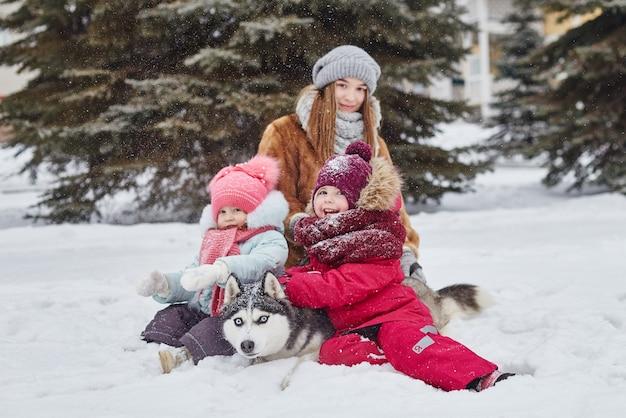 Зимой дети выходят на улицу и играют с хаски. дети сидят на снегу и гладят собаку хаски. гулять по парку зимой радость и веселье, собака хаски с голубыми глазами. россия, свердловск, 28 дек 2017 г.