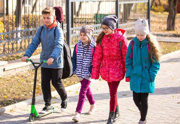 Дети ходят в школу на тротуаре с веселой компанией.