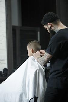 子供の美容師が暗い背景に小さな男の子をカットします。髪を切って満足しているかわいい幼児男の子。