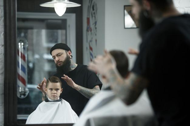 Детский парикмахер режет маленького мальчика на темном фоне.