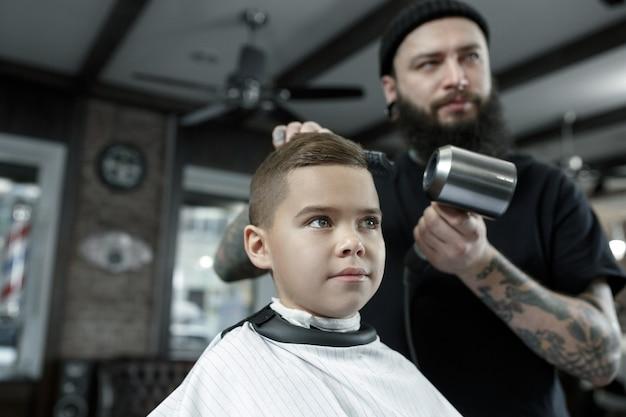 暗い背景に対して小さな男の子をカットする子供の美容師。