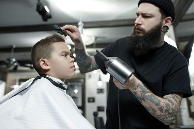Детский парикмахер режет маленького мальчика на фоне темноты