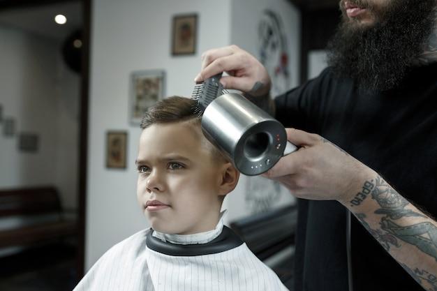 Parrucchiere di bambini taglio ragazzino contro uno sfondo scuro.