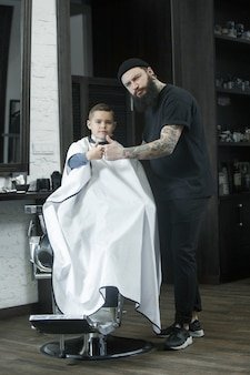 Children hairdresser cutting little boy against a dark background.