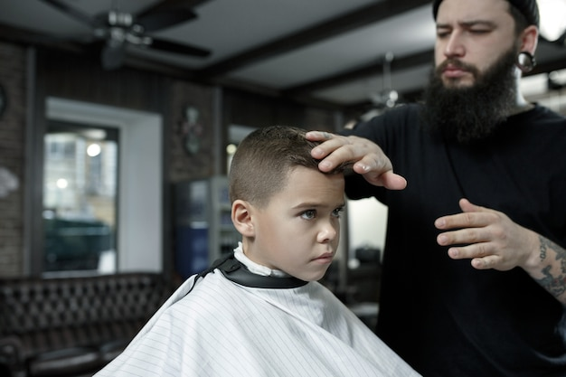 Children hairdresser cutting little boy against a dark