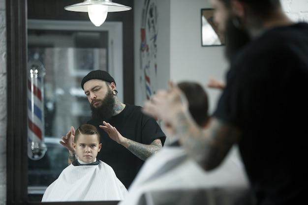 Children hairdresser cutting little boy against a dark