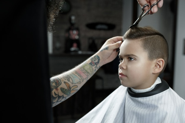 Children hairdresser cutting little boy in a barbershop