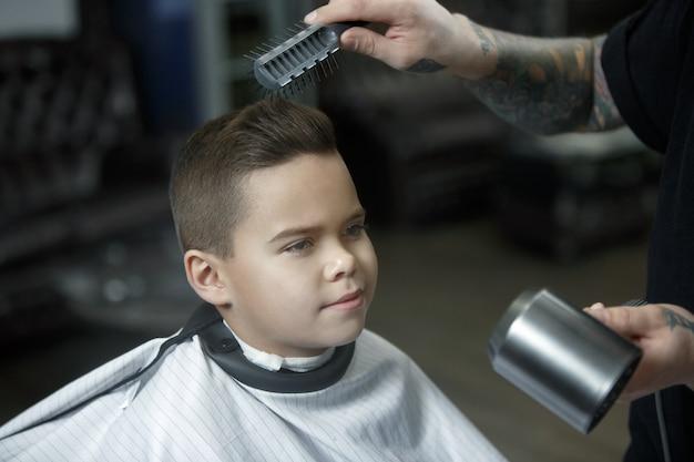 Parrucchiere di bambini taglio ragazzino in un negozio di barbiere