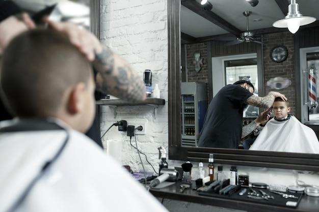 理髪店で小さな男の子を切る子供の美容師
