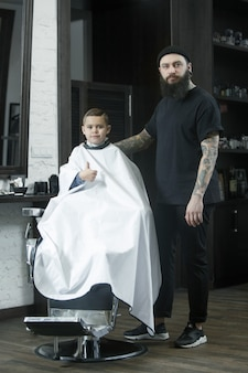 Children hairdresser cutting little boy.