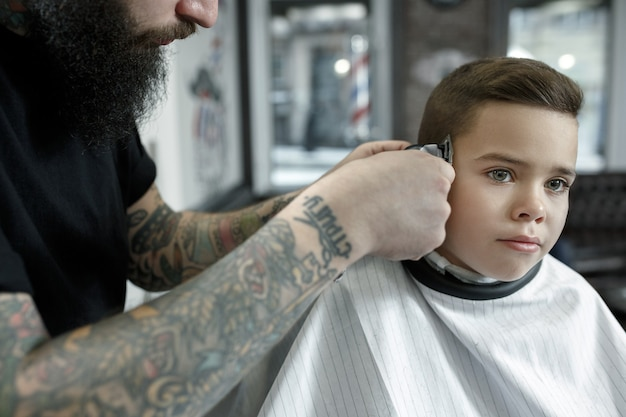 Children hairdresser cutting little boy