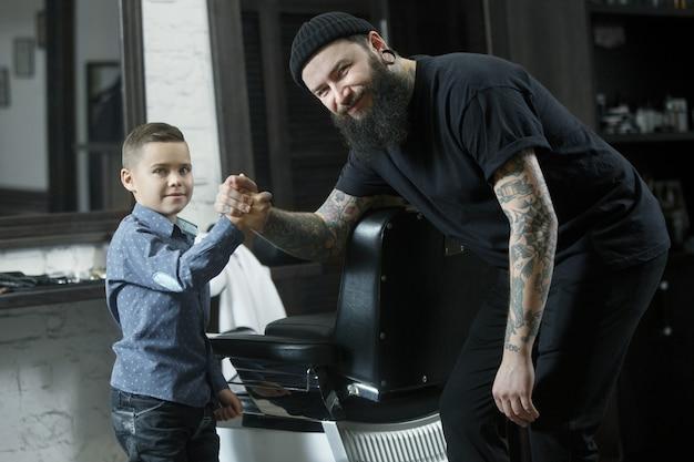Children hairdresser and little boy against dark