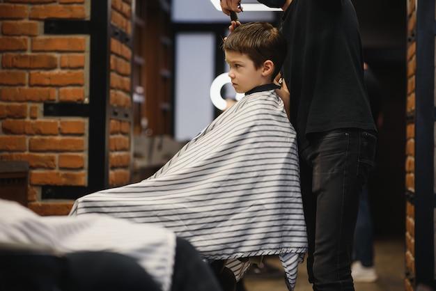 はさみを持つ子供の美容師は、暗い背景に対して小さな男の子をカットしています。散髪をしている満足のいくかわいい未就学児の男の子。