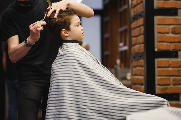 Children hairdresser with scissors is cutting little boy against a dark background. contented cute preschooler boy getting the haircut.