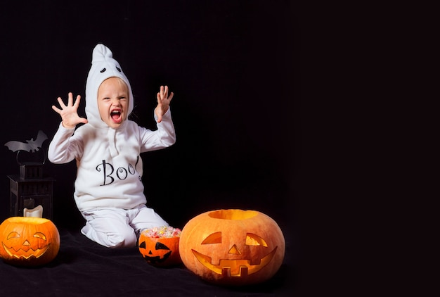 Children in halloween ghost costume makes a scary face on the black background with pumpking