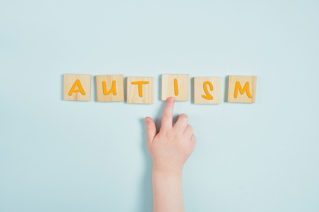 Children hand and autism on wooden squares blue background top view