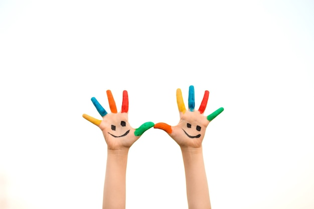 Children hand in colorful paint with smile isolated on white