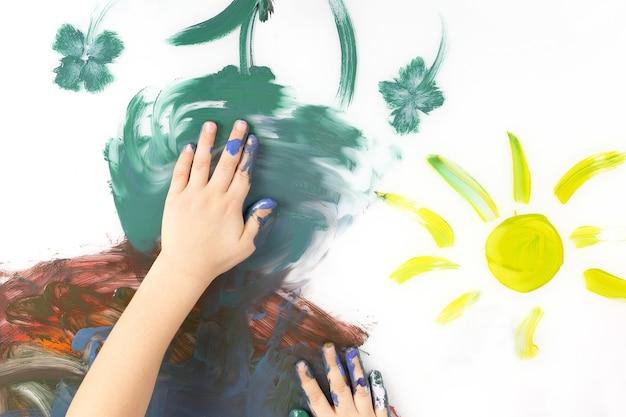 아이들은 흰색 바탕에 물감으로 그림을 손으로 그립니다. 아이들의 창의력과 취미