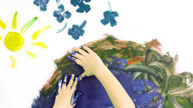 아이들은 흰색 바탕에 물감으로 그림을 손으로 그립니다. 어린이 그림의 창의성