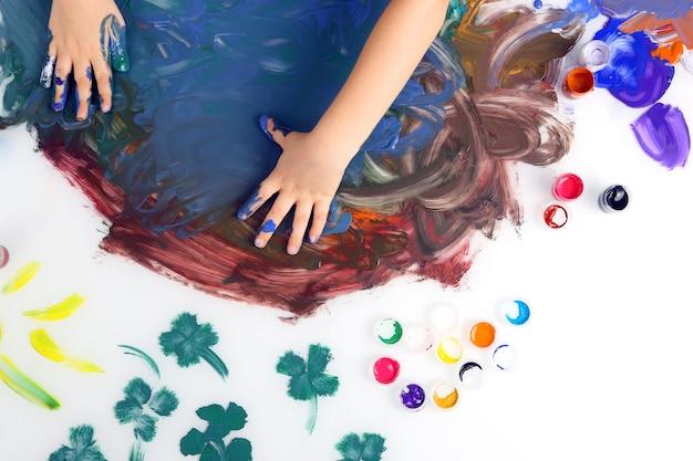 어린이 손 흰색 표면에 페인트로 그림을 페인트
