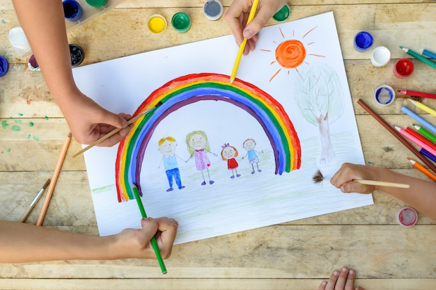 Children hands draw on a sheet of paper