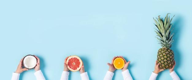 子供の手は青い背景にココナッツ、グレープフルーツ、オレンジ、パイナップル全体を保持します