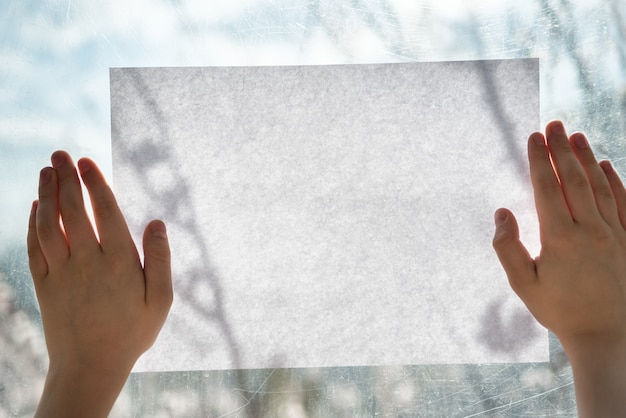 Children hands holding clean white sheet of paper on window pane.