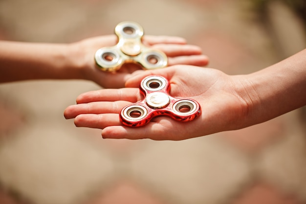Children hands holding fidgqet hand spinners. trendy and popular toy for children and adult.