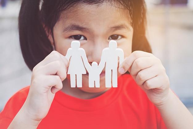 Руки детей, держа маленькую модель семьи, концепция семьи