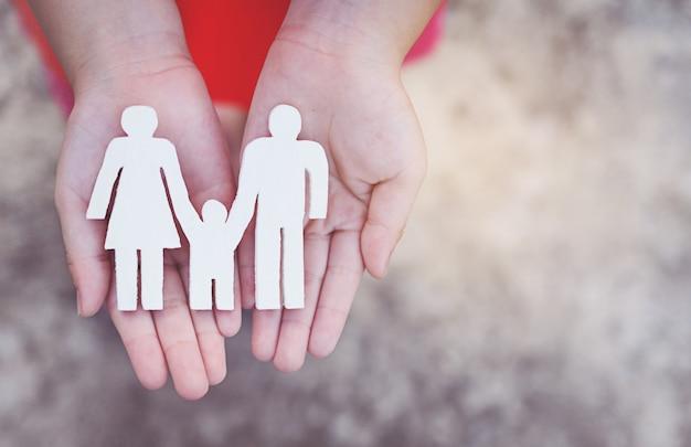 Детские руки держат маленькую модель семьи