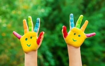 Children hands in colors. Summer photo. Selective focus.