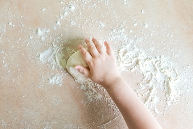 Children hands make dough