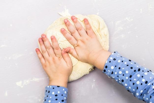 Children hands make a dough