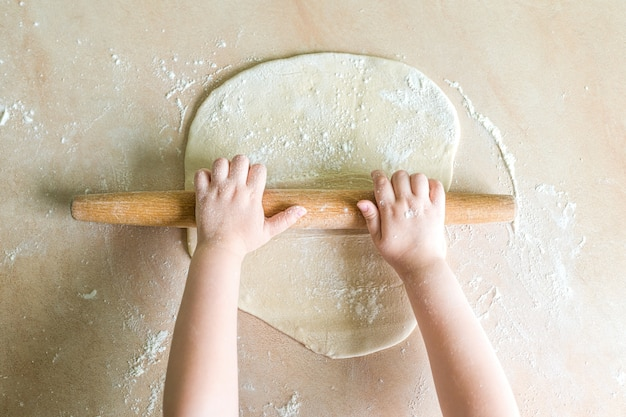 Children hands rolled dough
