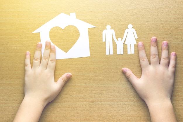 Children hands with small model of house and family on wooden background
